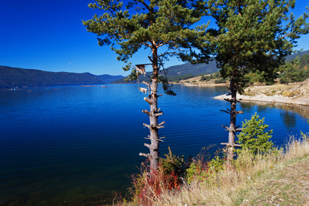 Mountain lake. A dam lake on the clear blue sky background. photo