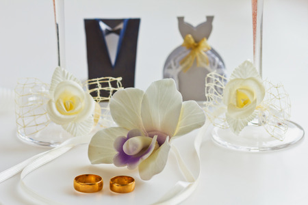 Two wedding rings  on white with orchids for background photo