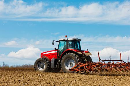 Bauer pflügt das Feld Anbau Zugmaschine im Bereich Rote Traktor mit einem Pflug in einem Bauernhof-Feld Traktor und Pflug