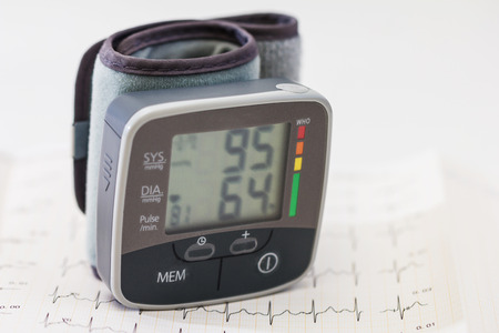 sphygmonanometer: Blood pressure device with cardiogram background Stock Photo