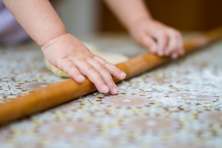 Hands baking dough with rolling pin on table. little chef  bake in kitchen.
