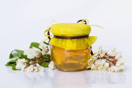 Acacia honey on white background. Robinia pseudoacacia