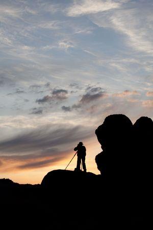 山の上のカメラマンのシルエット