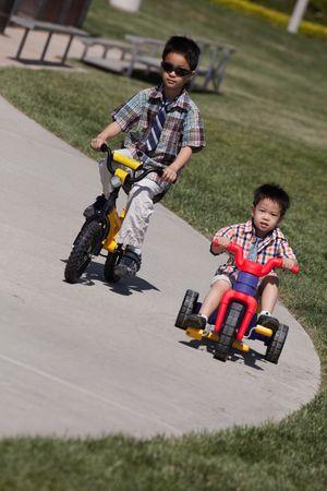 公園で一緒に自転車に乗って 2 人のかわいい男の子 写真素材