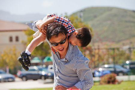 父は彼の肩に彼を置くことによって彼の幼い息子と遊ぶ