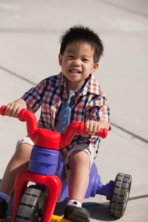 Cute three years old little boy riding a 3-wheel bike photo