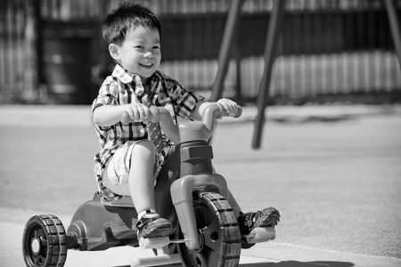 Cute three-year-old little boy riding a 3-wheel bike in playground photo