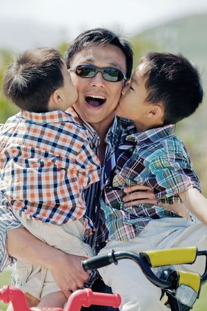 Two boys kissing their fathers cheeks while he holds them in his arms