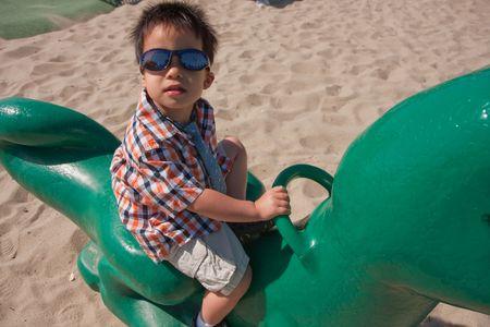 かわいい男の子は子供の遊び場におもちゃ竜に乗ってください。