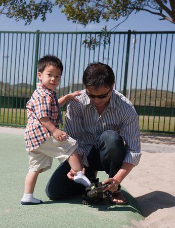 父は彼の靴に砂をダンプする彼の息子を助けています。