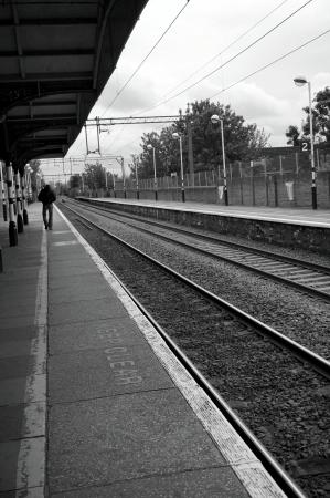 Man walking beside train tracks Stock Photo