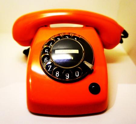 Old orange telephone with phone dials Stock Photo
