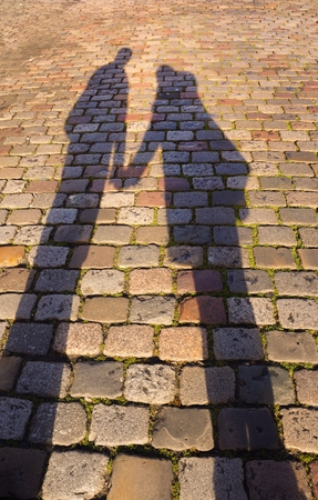 Shadows of couple holding hands Stock Photo