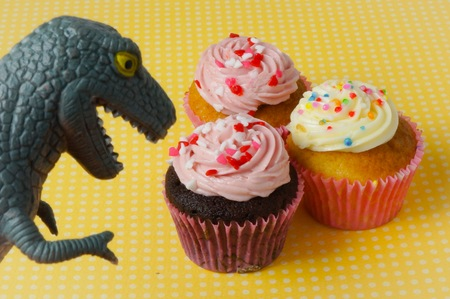 Cupcakes with yellow polka dot background and a dinosaur toy Stock Photo