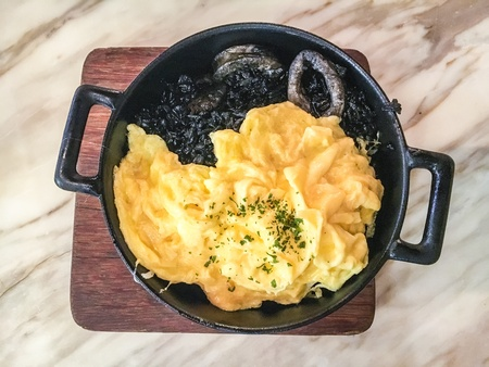 Squid ink rice with omelette Stock Photo