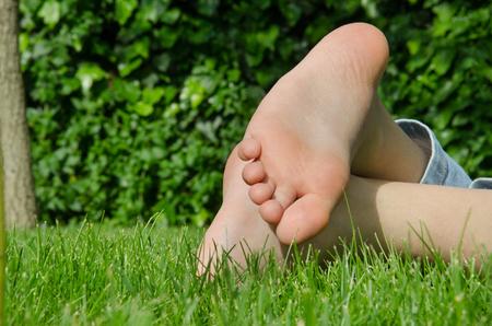 adolescentes chicas: Los pies descalzos de la hierba verde de verano de relax