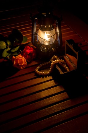 red oil lamp: Rose and pearl necklace in front of the oil lamp