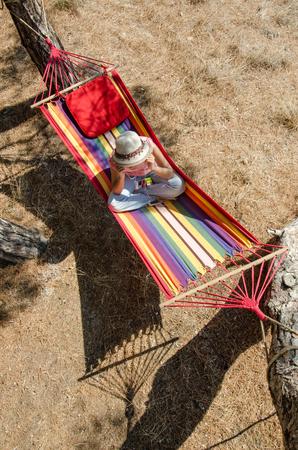 english ethnicity: listening music on the hammock Stock Photo