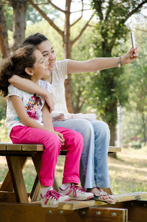 english ethnicity: Two Girls Taking Self With Mobile Phone