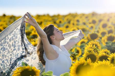 viento: Al aire libre de la muchacha en campo de girasol de primavera