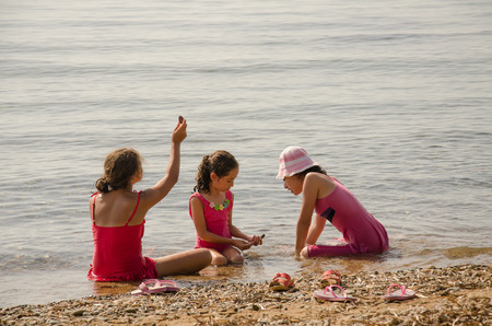english ethnicity: Children looking for pebbles at the seaside for their collections