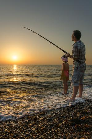 farther: Fishing on Beach Stock Photo
