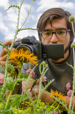 mountain peek: Hiker photographer to take a picture of flowers in mountains