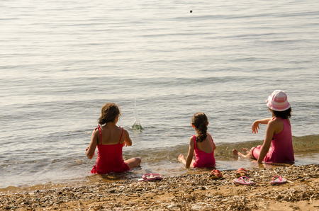 english ethnicity: Little girls throws rocks into the sea