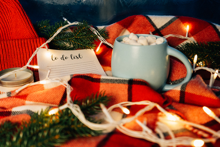 To do list. Beautiful Christmas holiday concept. Cup of hot coffee with marshmellow and Christmas lights on the red plaid background. Planning.