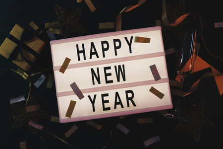 Happy New Year sign displayed on a lightbox with confetti decoration on black background. New Years Eve party. Flat lay. Top view. Holiday concept. 2019