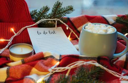 To do list. Beautiful Christmas holiday concept. Cup of hot coffee with marshmellow and Christmas decoration on the red plaid background. Planning.
