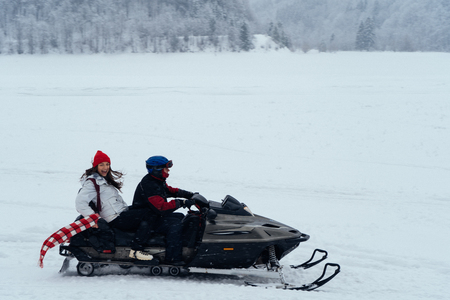 Side view of man and woman riding fast on a snowmobile on the frozen lake in the mountains with the scenic view. Pine trees covered with snow