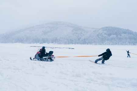 Snowboarder ride on a snowmobile holding a rope. On the frozen lake between beautiful snowy forest. Extreme sport