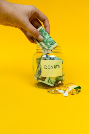 Donation jar with paper money and coins on yellow background. Pills and medicine. Womans hand putting dollar bill into the jar