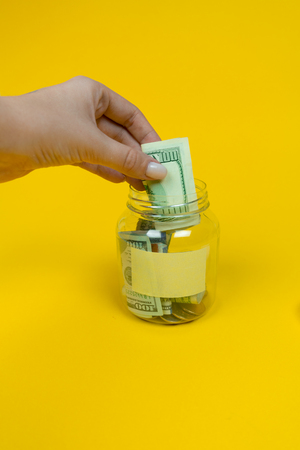 Womans hand put one hundred dollar bill into the money jar. Sticker for your text. Copy space. Isolated on yellow background