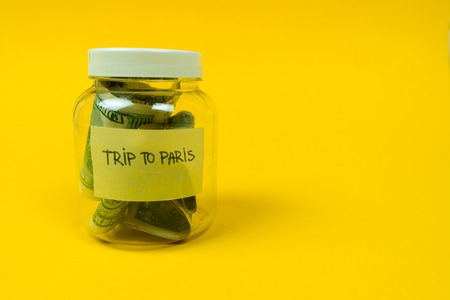 Money jar with coins and dollars isolated on yellow background. Saving for Travel. Travel to Paris