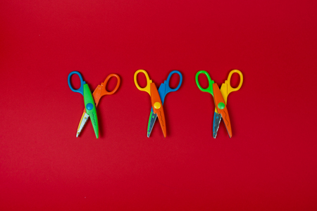Safety colorful scissors isolated on red background. Three colorful kids scissors.