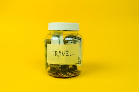 Money jar with coins and paper dollars isolated on yellow background. Saving for Travel.
