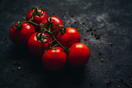 Beautiful fresh tomatoes on a branch isolated on black table background. Ripe organic vegetables. Vegetarian food