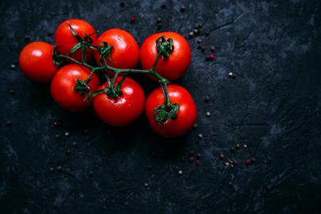 Top view of beautiful fresh organic tomatoes on branch isolated on black sony background. Healthy ripe vegetables