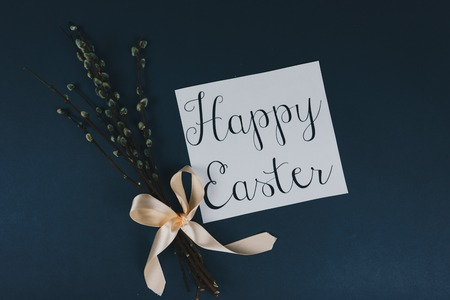 Flat lay of willow branches and Happy Ester greeting card isolated on blue background. Spring and Easter concept