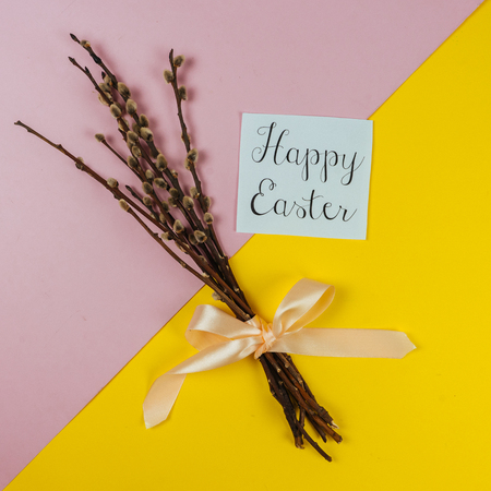 Willow branches and Happy Ester greeting card isolated on yellow and pink background. Spring and Easter concept. Top view. Square image