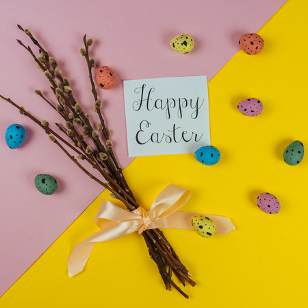Happy Ester greeting card, willow brunches and painted quail eggs isolated on yellow and pink background. Spring and Easter concept. Top view