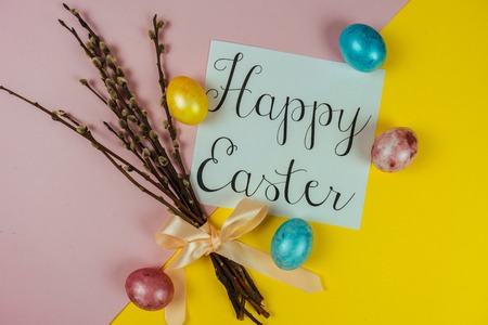 Happy Ester greeting card, willow brunches and painted eggs isolated on yellow and pink background. Spring and Easter concept. Top view