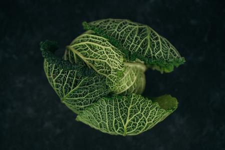 Verza cruda fresca isolata sul fondo nero della tavola. Cibo vegetariano. Verdure sane. Vista dall'alto