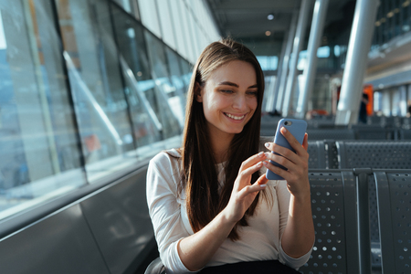 Traveler woman sitting at the gate and using smartphone while waiting for a flight at the airport. Travel concept. Young passenger girl chatting and smiling in terminal departure lounge.