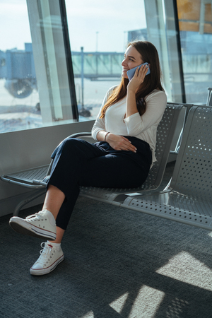 Young woman in casual clothes sitting at the airport departure lounge and talking on the cell phone while waiting for a flight. Travel concept. Passenger girl having a conversation on mobile phone.