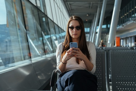 Young beautiful woman in sunglasses sitting at the airport terminal departure lounge and using smartphone while waiting for a flight. Travel concept. Travel passenger girl chatting on mobile phone.