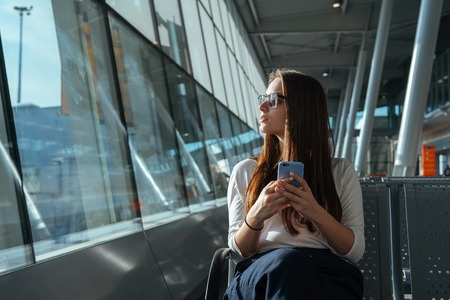 Passenger woman in casual clothes sitting at the gate and using smartphone while waiting for a flight at the airport. Travel concept. Girl chatting in terminal departure lounge.