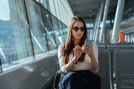 Young beautiful woman in casual clothes sitting at the airport terminal departure lounge and using smartphone while waiting for a flight. Travel concept. Passenger girl chatting on mobile phone.